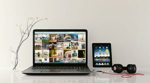 photo of laptop, tablet, ear phones